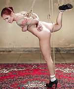 Beautiful redhead is taken down and tied tight in brutal rope bondage